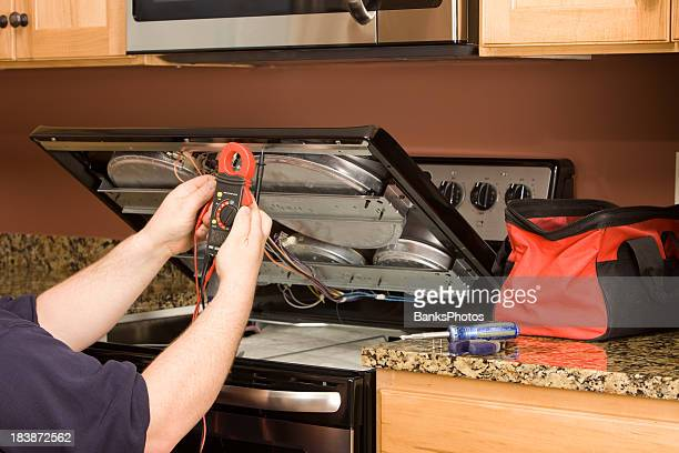 Appliance Repairman Using Multimeter on a Kitchen Range