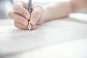 Woman hand writing on paper, fill in empty document template applying for job, resume.