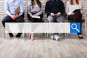 Close-up Of Business People Sitting On Chair Waiting For Job Interview In Office