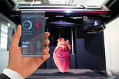 Hand with futuristic transparent smartphone. Application for printing human organs in a 3D printer.