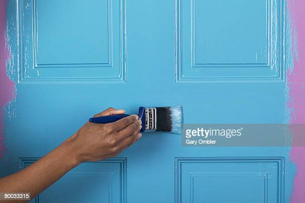 Applying blue paint to a door with a brush