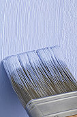 Applying blue paint to a wall with a brush, close up