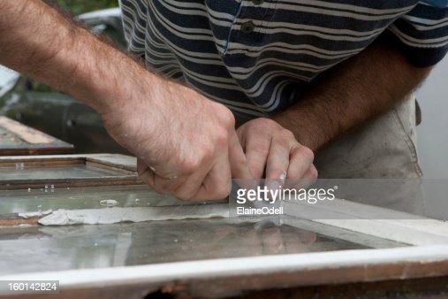 Applying glazing to old window. : Stock Photo