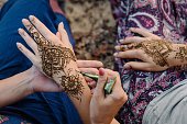 Applying henna tattoo on women hands. Mehndi is traditional Indian decorative art. Close-up, top view