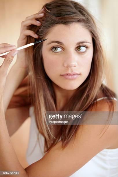 Applying her eyeliner