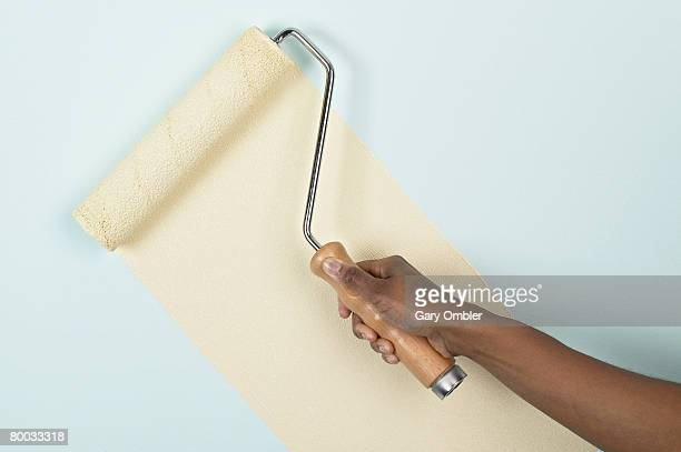 Applying paint to a wall with a roller