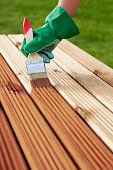 Applying protective varnish on a patio wooden floor. garden concept