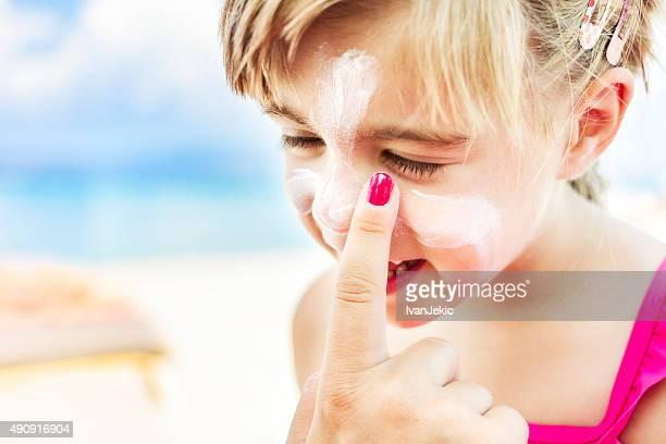 Aplicação de protector solar para criança rosto