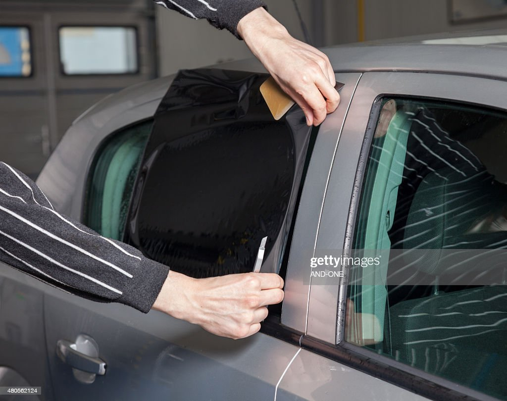 Applying tinting foil on a car window : Stock Photo