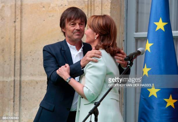 Appointed French Ecology Minister Nicolas Hulot hugs outgoing French Minister for Ecology Sustainable Development and Energy Segolene Royal during an...