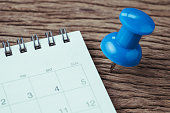 Appointment, deadline, holiday or date planning concept, big blue pushpin or thumbtack pin on wooden table next to white clean calendar.