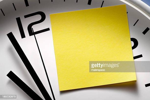 Appointment reminders. Clock with yellow sticky note.