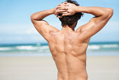 Rear view of an attractive young man looking out at the ocean