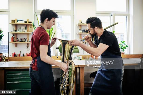 Apprentice Assisting Master Craftsman, Applying Final Adjustments To Musical Instrument