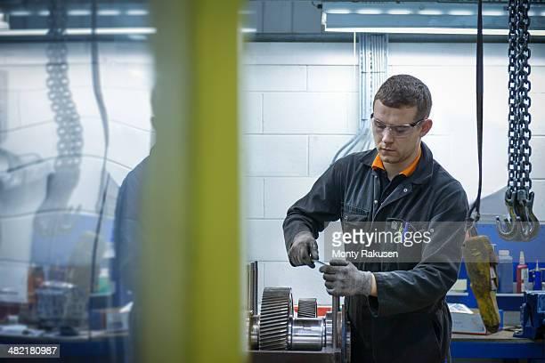 Apprentice engineer assembling industrial gearbox in factory