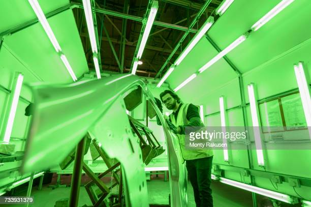 Apprentice engineer inspecting steel car body parts in green lit area of car factory