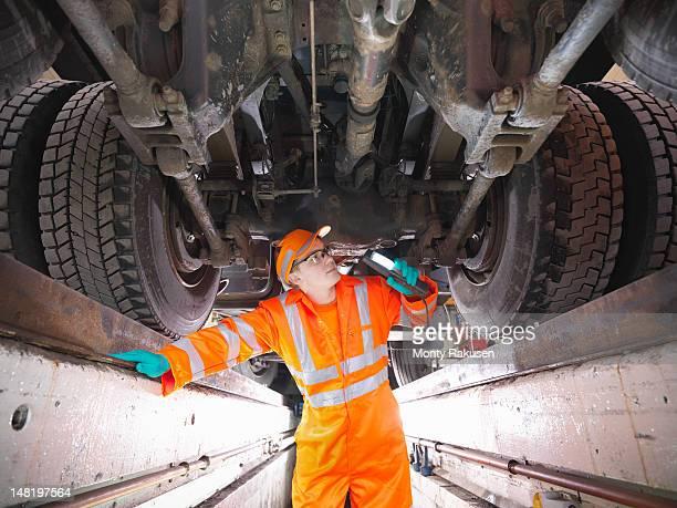 Apprentice engineer inspecting underneath truck