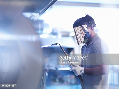 Apprentice glass blower wearing mask and using lance