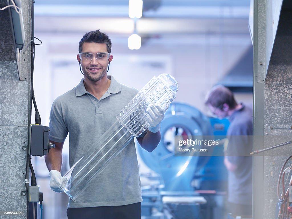 Apprentice glass blower with complex glass part, portrait