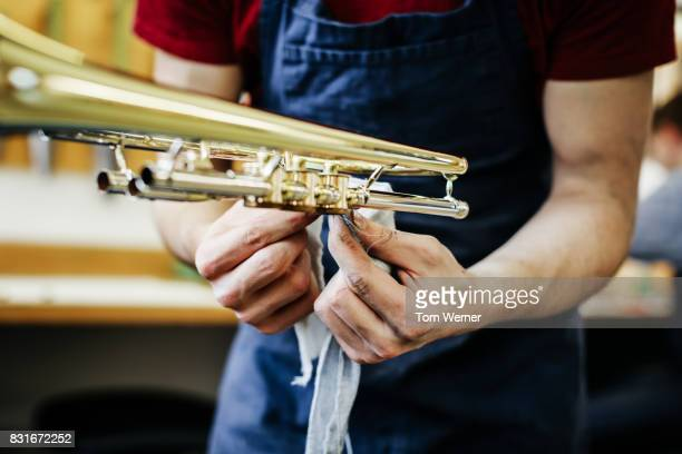 Apprentice Polishing Newly Built Musical Instrument In Workshop