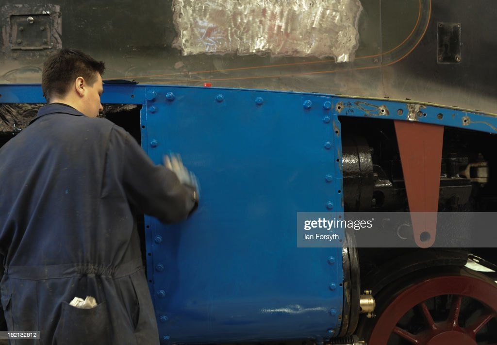 Apprentice Steve Foxton, 31, from Spennymor cleans fresh paintwork on the locomotive Dominion of Canada as it undergoes restoration work on February 19, 2013 in Shildon, England. The Doncaster built engine which has come to the UK from Montreal, Canada is receiving a 'Mallard-style' makeover at the National Railway Museum at Shildon in time for the 75th anniversary celebrations of Mallard breaking the world steam speed record.