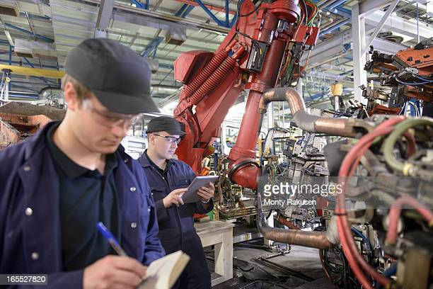 Apprentices inspecting robots in car plant