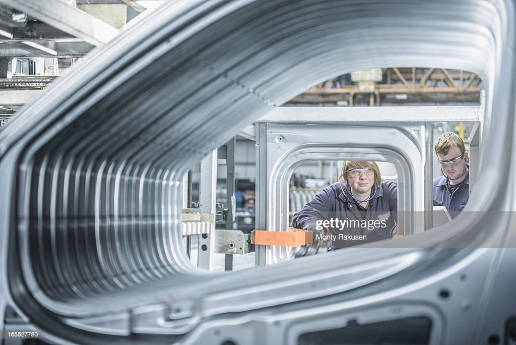 Apprentices inspecting section of car body in car plant
