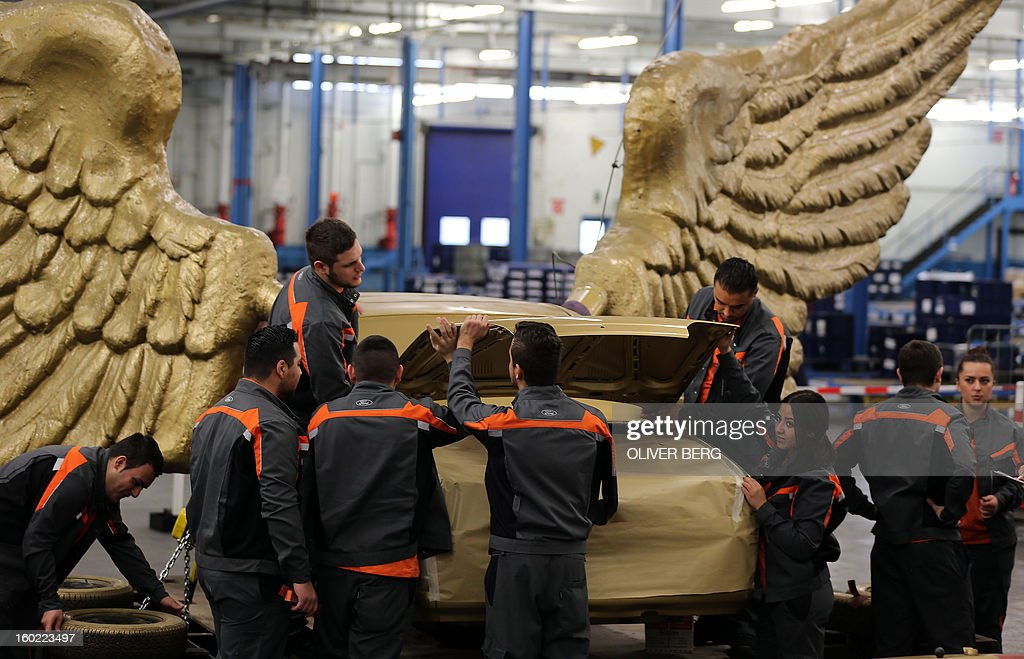Apprentices of the Ford car manufacturer restore parts of the 'Fluegelauto' (winged car) art work by German installation, happening and conceptual artist HA Schult (born Hans-Juergen Schult) on January 28, 2013 at the company's plant in Cologne, western Germany. The golden winged car, created in 1991 as part of the performance 'Fetisch Auto' (fetish car), will turn back on the roof of the Koelnisches Stadtmuseum (Museum of the City of Cologne) in spring 2013, when restoration is finished. AFP PHOTO / OLIVER BERG GERMANY OUT