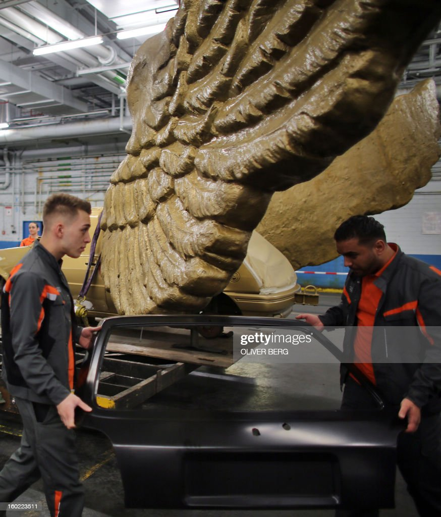 Apprentices of the Ford car manufacturer restore parts of the 'Fluegelauto' (winged car) art work by German installation, happening and conceptual artist HA Schult (born Hans-Juergen Schult) on January 28, 2013 at the company's plant in Cologne, western Germany. The golden winged car, created in 1991 as part of the performance 'Fetisch Auto' (fetish car), will turn back on the roof of the Koelnisches Stadtmuseum (Museum of the City of Cologne) in spring 2013, when restoration is finished.