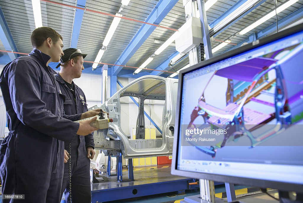 Apprentices wearing boiler suits measuring car body in car plant, computer image on monitor in foreground