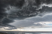 Landscape photo of a beach and dramatic thunderstorm clouds over the sea or the ocean