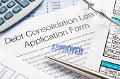 'Approved Debt Consolidation Loan Application Form with pen, calc'