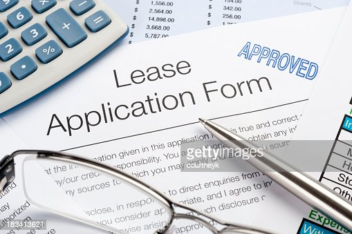 Approved Lease Application Form with pen, calculator, writing ha