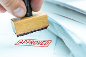 man stamping approved documents or project, shallow depth of field, focus on stamp