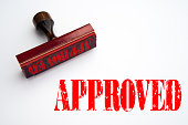 A 3d rendering of a rubber stamp with the word 'approved'