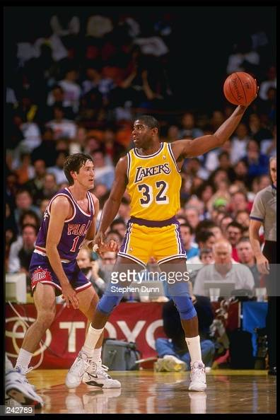 Guard Magic Johnson of the Los Angeles Lakers keeps the ball away from guard Jeff Hornacek of the Phoenix Suns during a game at the Great Western...