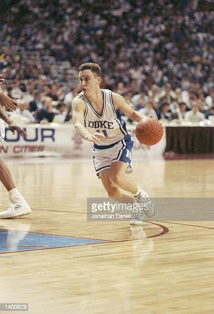 Guard Bobby Hurley of the Duke Blue Devils dribbles the ball down the court during a playoff game against the Michigan Wolverines at the Hubert H...
