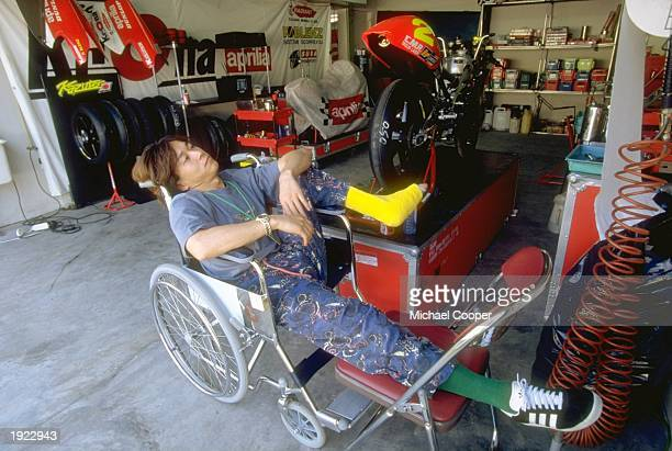 Aprilia rider Kazuto Sakata of Japan relaxes in a wheelchair with a broken foot during the Indonesian Grand Prix at the Sentul circuit in Indonesia...