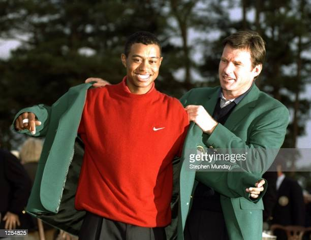 1996 US Masters winner Nick Faldo of Great Britain helps 1997 winner Tiger Woods of the USA put on the Green Jacket after Woods won the US Masters at...
