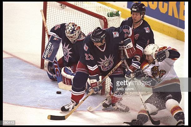 Goal tender Mike Richter of the New York Rangers keeps the puck out of the goal with help from teammates Jeff Beukeboom and Adam Graves during their...