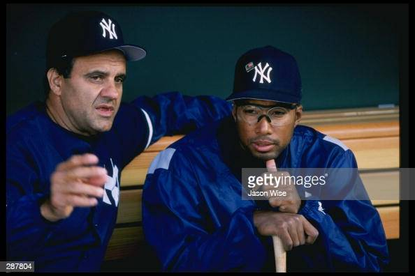 Manager Joe Torre of the New York Yankees talks to player Bernie Williams in the dugout during the Yankees 125 victory over the California Angels at...