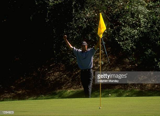 Tiger Woods of the USA celebrates as he chips in at the 12th during the first day of the US Masters at Augusta Georgia Woods went on to win the...