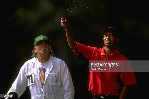 Tiger Woods of the USA checks the wind direction watched by his caddie Mike 'Fluff' Cowan on the final day of the US Masters at Augusta Georgia Woods...