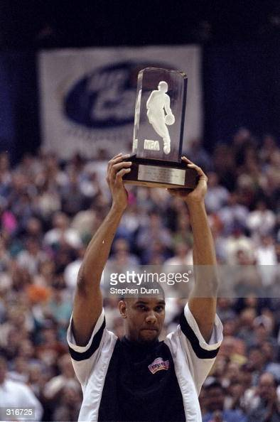 Center Tim Duncan of the San Antonio Spurs holds his Rookie of the Year trophy during an NBA playoff game against the Phoenix Suns at the AlamoDome...