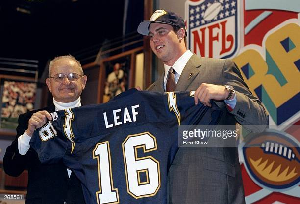 Second overall pick Ryan Leaf shows off his jersey alongside Alex Spanos after being selected by the San Diego Chargers in the first round of the...