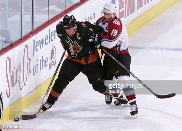 Joe Sakic of the Colorado Avalanche holds back Jeremy Roenick of the Phoenix Coyotes in the first period during game five of the first round of...