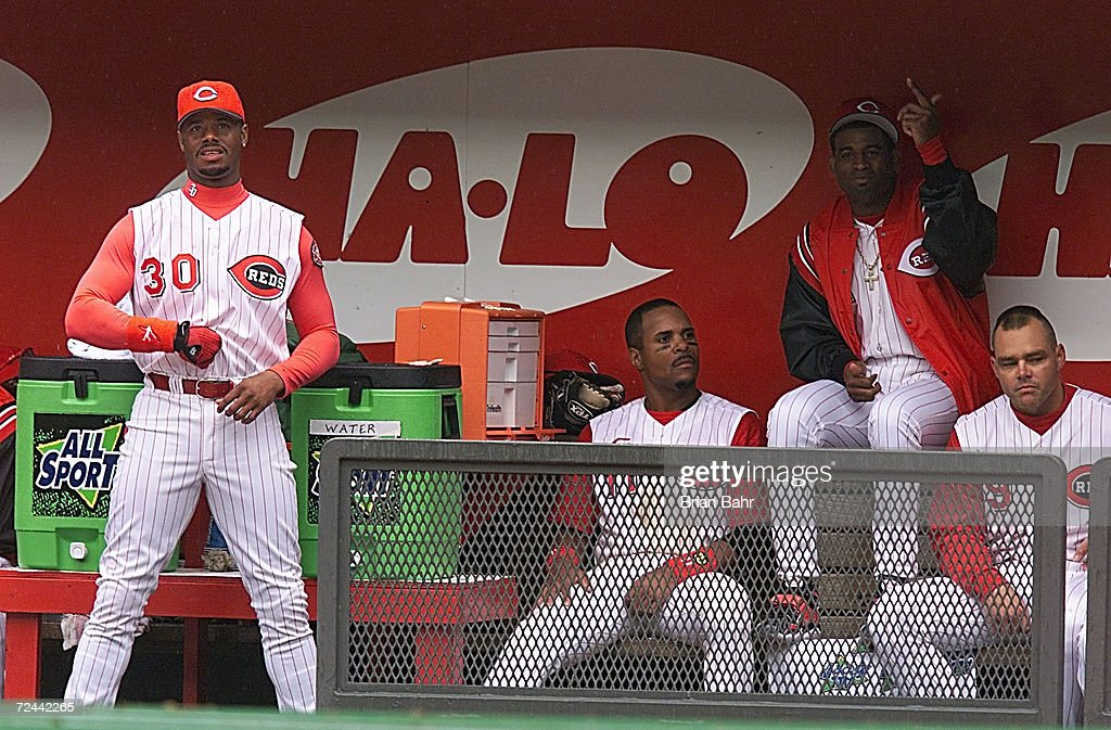 New Cincinnati Reds players Ken Griffey, Jr. #30, Deion Sanders #2 (atop the bench) and Dante Bichette #9 joke around between innings on opening day at Cinergy Field in Cincinnati, Ohio. X <DIGITAL