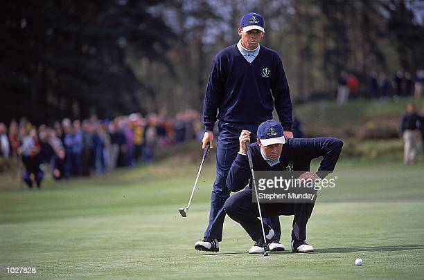 Sergio Garcia of Spain and Continental Europe looks on as Jan Van De Velde of France and Continental Europe kneels down during the Greensomes during...