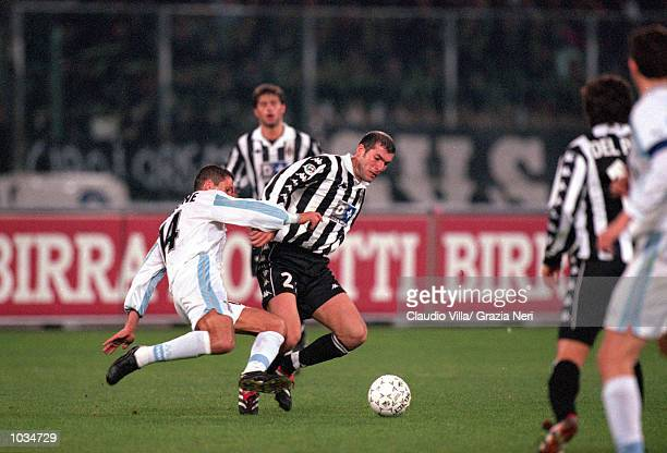 Zinedine Zidane of Juventus holds the ball from Diego Simeone of Lazio during the Italian Serie A match played at the Stadio Delle Alpi in Turin...