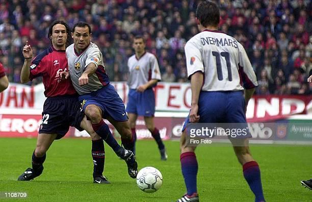 Barjuan Sergi of Barcelona passes the ball to Marc Overmars under pressure from Alex of Osasuna during the Osasuna v Barcelona La Liga match played...